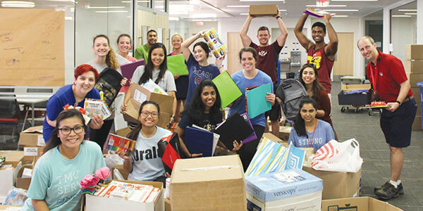 Students box donated school supplies.