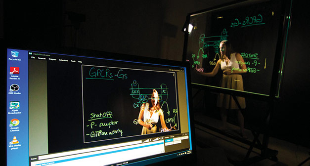 Professor Jennifer Bryant using a lightboard with her laptop in foreground.