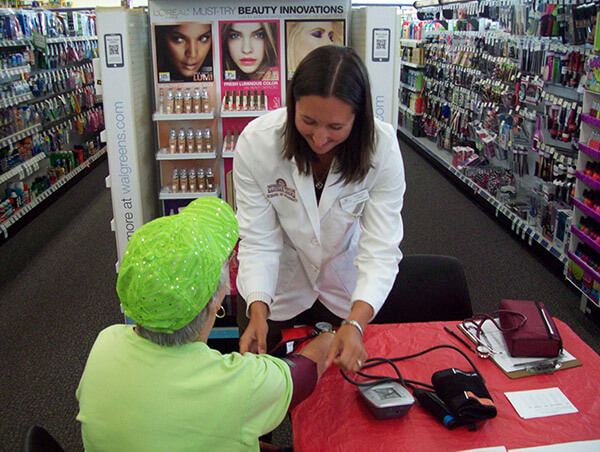 Pharmacist checking patients blood pressure.