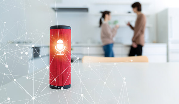 Smart speaker in foreground with man and woman facing each other in background.