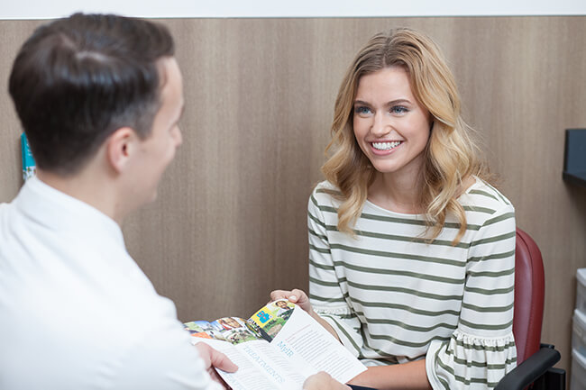 Pharmacist hands patient an informational tri-fold.
