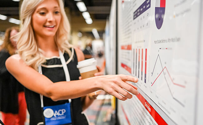 Conference participant point to a chart on a research poster.